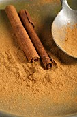 Ground cinnamon and cinnamon sticks, with a spoon