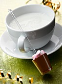Hot milk with a stick of chocolate
