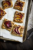 Puff pastry squares with red plum crumble on a baking sheet