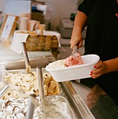 An ice cream shop assistant filling a plastic container with ice cream