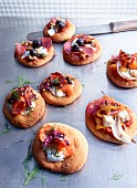 Assorted mini pizzas with salami, salmon and peppers