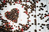 Red and black peppercorns in the shape of a heart