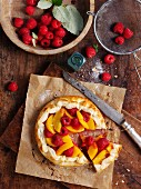Peach and raspberry tart, one slice cut