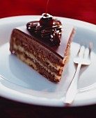 A slice of chocolate layer cake topped with cherries