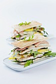 A club sandwich made with toasted crustless white bread, rocket, chicken, Parma ham, mango, parmesan and mayonnaise
