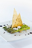 Green asparagus on wooden skewers with goat's cheese, balsamic vinegar and sheets of strudel pastry