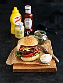 Hamburger with bacon, mayonnaise and pickled gherkins