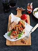 Pulled pork burger with sliced chillies and rocket