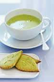 A cup of matcha tea with leaf-shaped matcha biscuits