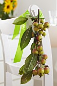Branch of crab apples tied to back of chair with satin ribbon