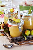 Apple sauce in small jars decorated with ornamental apples