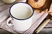 Old metal vintage cup of fresh milk with a glass and cookies on an rustic wooden table