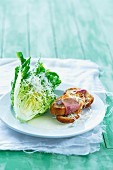 Lettuce with grated cheese, a yoghurt dressing and toasted baguette topped with bacon