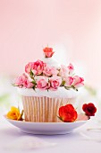 A large cupcake decorated with rosebuds