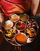 A woman holding a tray of assorted sauces from India