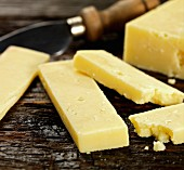 Chunks of cheddar and a cheese knife on a wooden surface