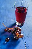 Red wine grapes and grape juice on a bllue wooden tabletop
