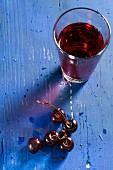 Cherries and cherry juice on a blue wooden tabletop