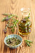 Olive oil with hyssop, and fresh hyssop on a wooden surface