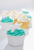 Cupcakes decorated with green and yellow frosting and snowflakes