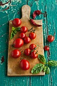 Tomatoes, basil and dried chillies on a chopping board