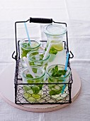 Several glasses of lemon juice with mint in a wire basket