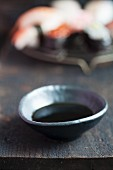 Soy sauce in a small dish in front of a plate of sushi (Japan)