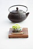 Wagashi hydrangea (ajisai) in front of a teapot (Japan)