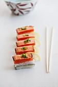 Oshi sushi with seared salmon, sliced spring onions (negi) and lemons (Japan)