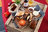 Wild boar burger in a bun with a grilled tomato and potato wedges, served on a wooden board