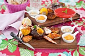 Surf 'n' turf (beef steak and lobster) with corn on the cob and stuffed potato skins, served on a wooden board