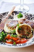 Potato cakes with spinach filling, tomato salad and parsley