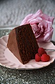 A slice of chocolate cake with raspberries and a rose for Valentine's Day