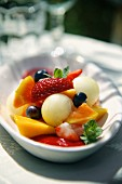 Fruit salad with melon balls and raspberry sauce