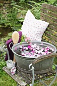 Water and rose petals in zinc tub on chair with scoop of rose bath salts