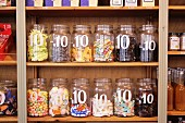 Assorted sweets in open storage jars, labelled with the price per item, on wooden shelving