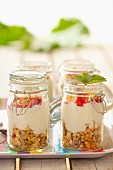 Muesli with oats, yoghurt, strawberries and flaked almonds, in jars
