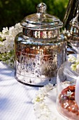 A silver jar, white lilac flowers and cakes on a table in the garden