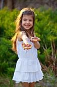 Little girl holding rhubarb tartlets in a garden