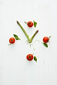 A clock face made from tomatoes and green asparagus