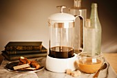 Fresh coffee in a coffee press alongside biscuits and a cup of coffee