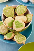 Bowl of apple-shaped biscuits with green icing