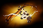 Splashes of milk and coffee with coffee beans