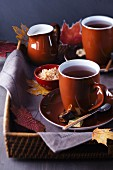 Tray of teacups, sugar and milk decorated with autumn leaves
