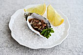 A fresh oyster with lemon wedges on rock salt
