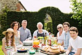 Multigenerational family sitting around table decked with food in a summer garden
