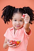 Portrait of Asian girl with ponytails holding candy