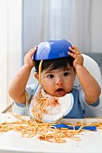 Baby boy in high chair with spaghetti bowl on his head