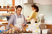 Woman decorating cupcakes in bakery