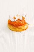 Sweet pastry topped with carrot & passion fruit spread and coconut shavings